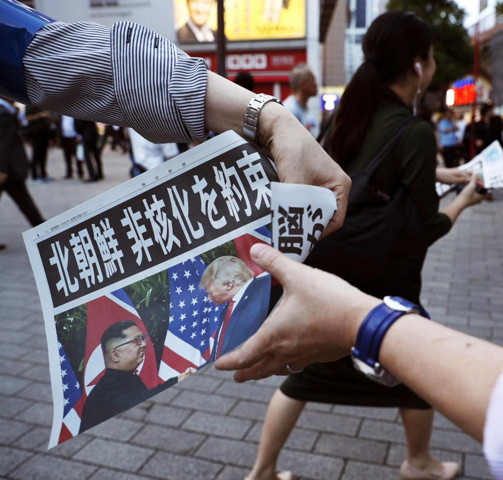 A staff of Japanese newspaper Mainichi Shimbun distributes their extra edition which report the summit between U.S. President Donald Trump and North K...