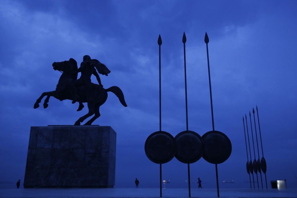 FILE - In this Wednesday, Oct, 8, 2014 file photo, a modern bronze statue of Alexander the Great is flanked by copies of round shields and the Macedon