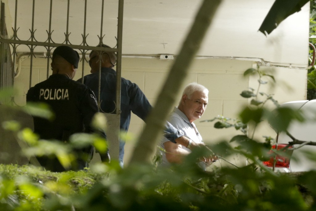 Former Panamanian President Ricardo Martinelli is escorted in handcuffs to a vehicle at El Renacer jail in the Gamboa area of Panama City, Monday, Jun