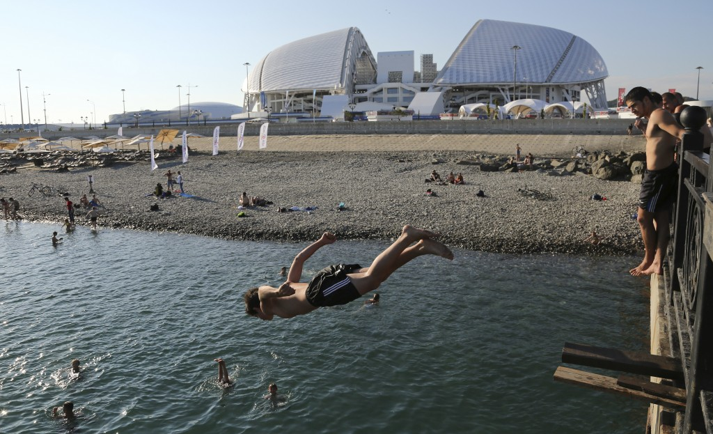 A boy jumps into the black sea in front of the Fisht stadium, which will host some 2018 World Cup matches in Sochi, Russia, Monday, June 11, 2018. (AP