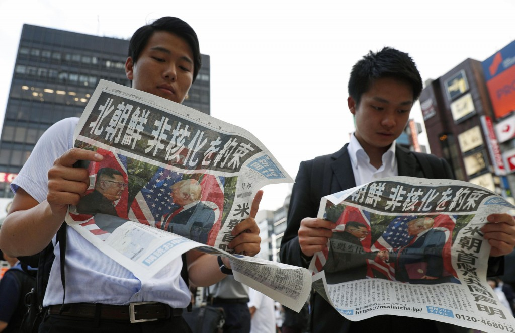 People look at the extra edition of  Japanese newspaper Mainichi Shimbun reporting the summit between U.S. President Donald Trump and North Korean lea
