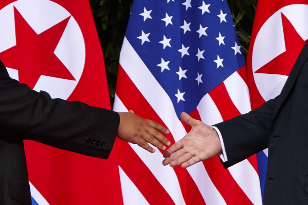 In this Tuesday, June 12, 2018, file photo, U.S. President Donald Trump, right, reaches to shake hands with North Korea leader Kim Jong Un at the Cape