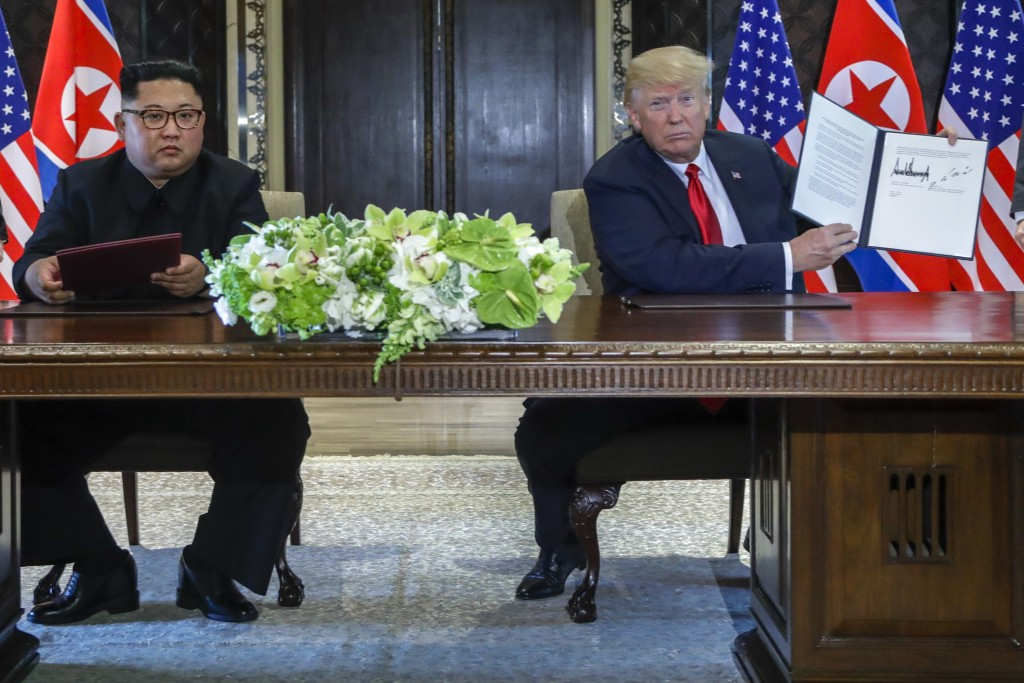 U.S. President Donald Trump holds up the document that he and North Korea leader Kim Jong Un just signed at the Capella resort on Sentosa Island Tuesd...