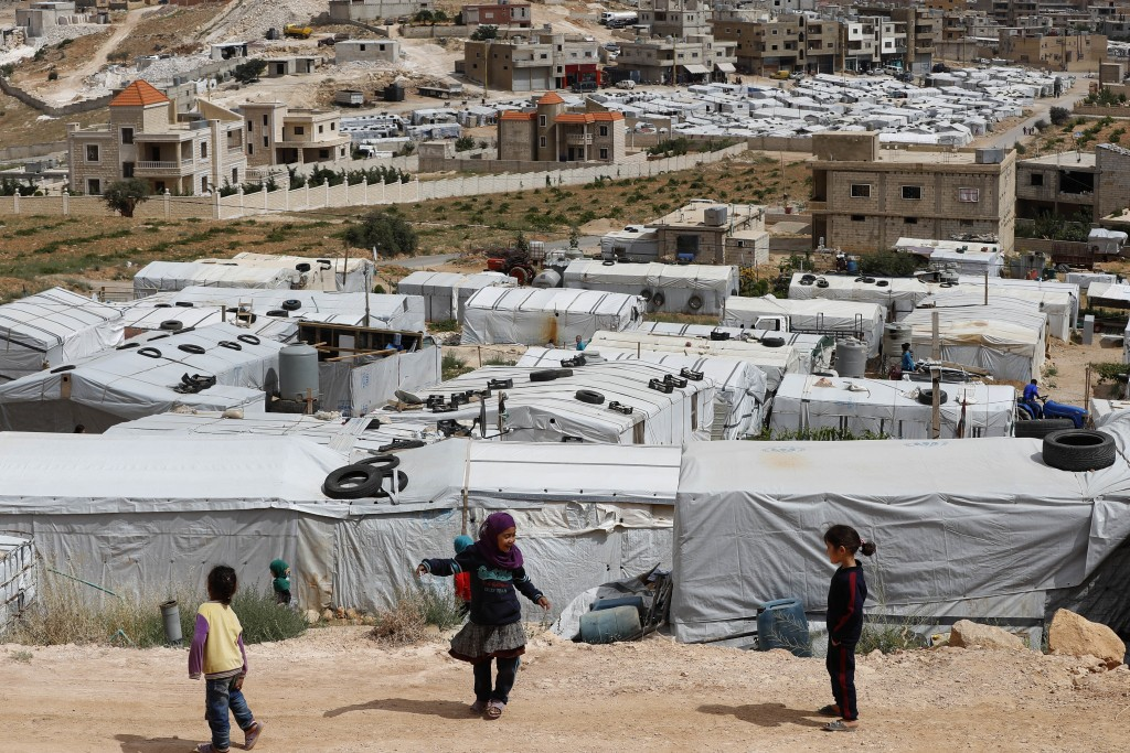 Syrian refugee children play at an informal refugee camp, which is seen set between the houses and buildings in Arsal, near the border with Syria, eas