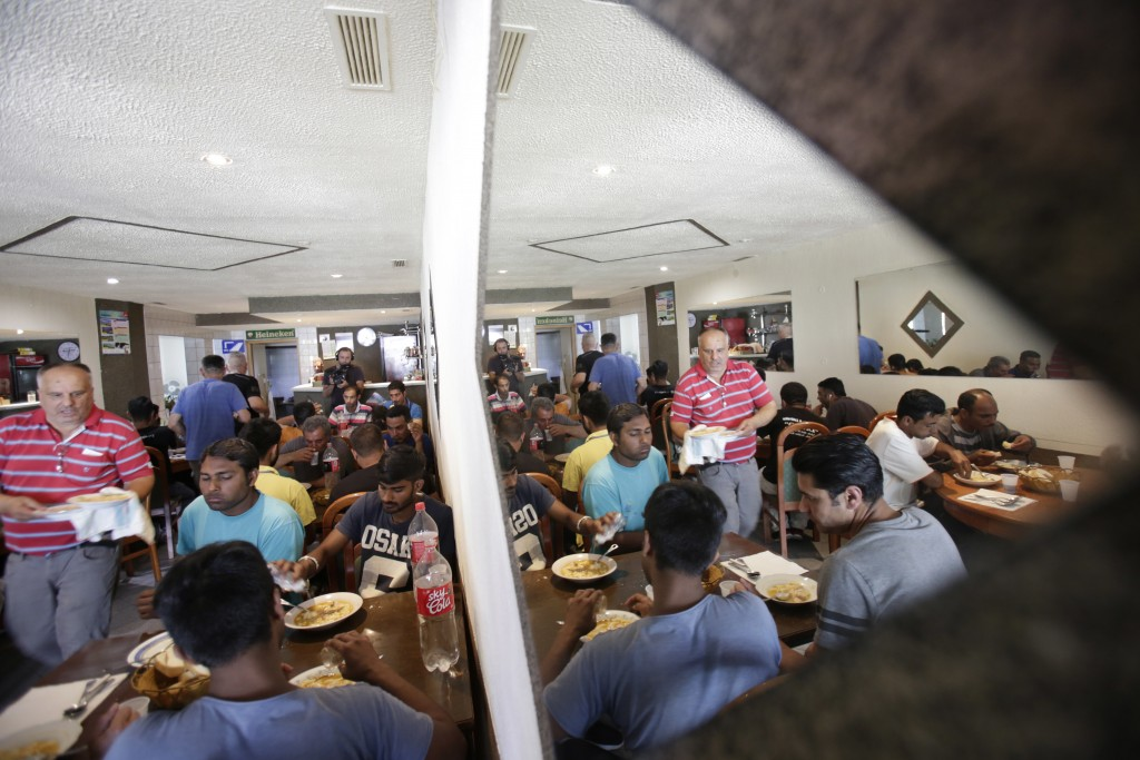 In this photo taken on Sunday, June 10, 2018, Bosnian Asim Latic, at left, serves food to migrants inside his restaurant, in Velika Kladusa, 400 kms n