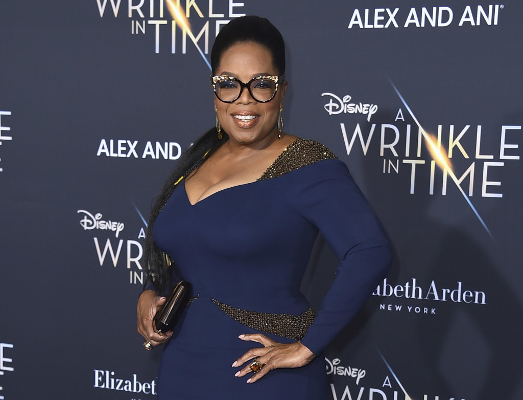 "FILE - In this Feb. 26, 2018 file photo, Oprah Winfrey arrives at the world premiere of ""A Wrinkle in Time"" in Los Angeles. Winfrey will serve as godm"