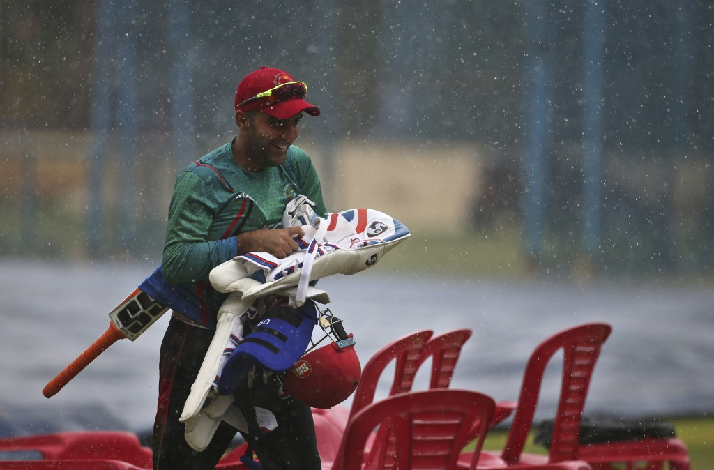 Afghanistan cricketer Hashmatullah Shahidi carries his gear as he runs for shelter during sudden rains at a training session ahead of one-off test mat