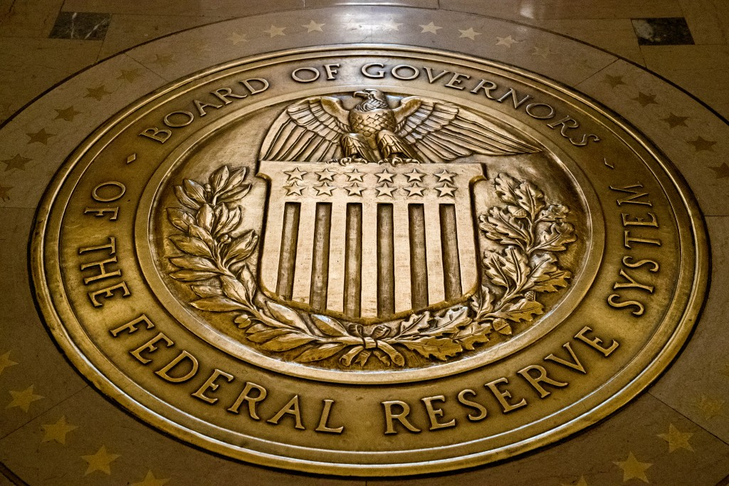 FILE- In this Feb. 5, 2018, file photo, the seal of the Board of Governors of the United States Federal Reserve System is displayed in the ground at t