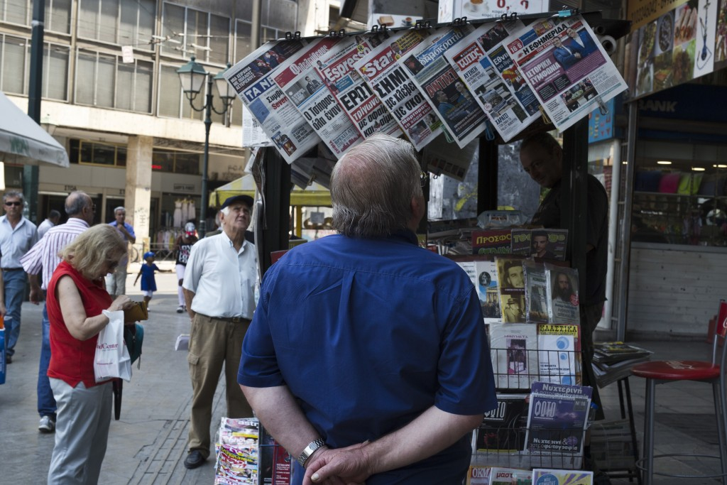 People read newspaper front pages a day after a Greek- Macedonian agreement, at a kiosk in Athens, on Wednesday, June 13, 2018. A historic deal ending