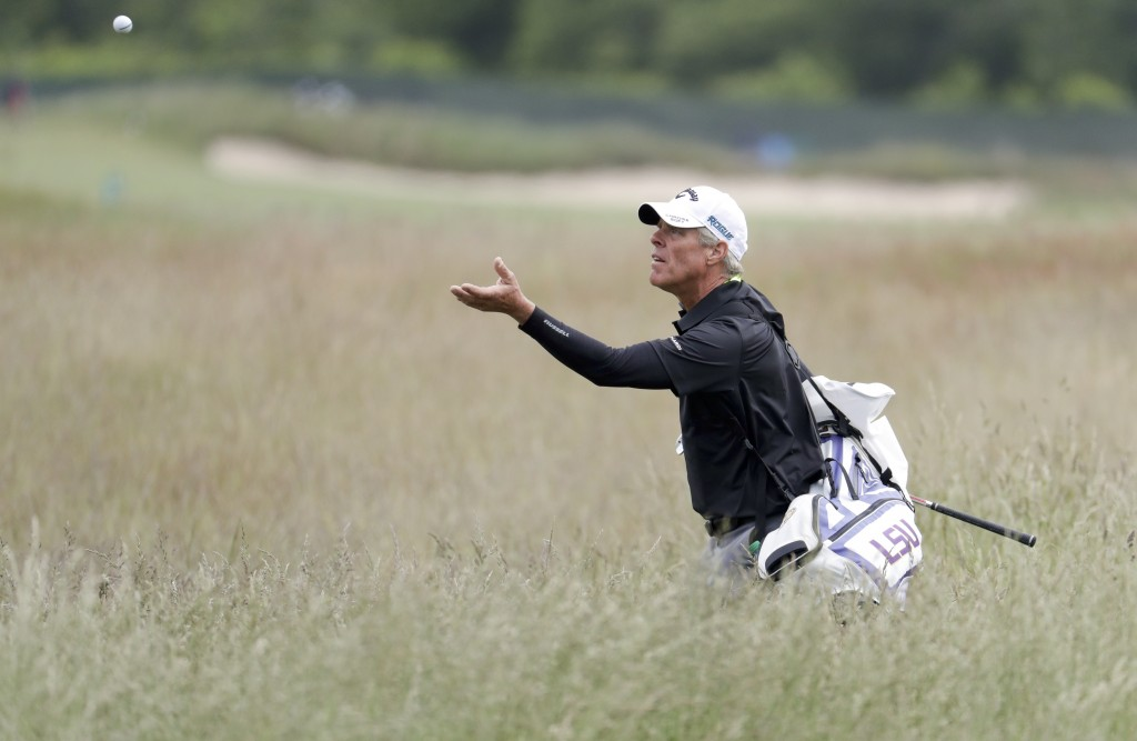 Luis Gagne's caddie turns to catch a ball as he walks through the fescue during a practice round for the U.S. Open Golf Championship, Wednesday, June