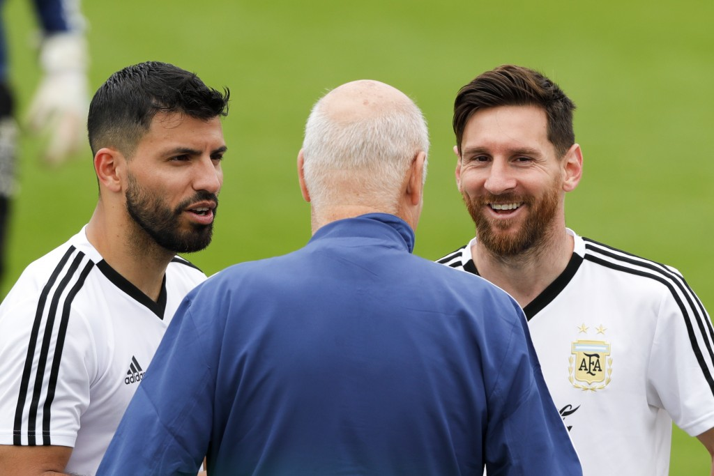 Lionel Messi, right, and Sergio Aguero talk to a team assistant during a training session of Argentina at the 2018 soccer World Cup in Bronnitsy, Russ