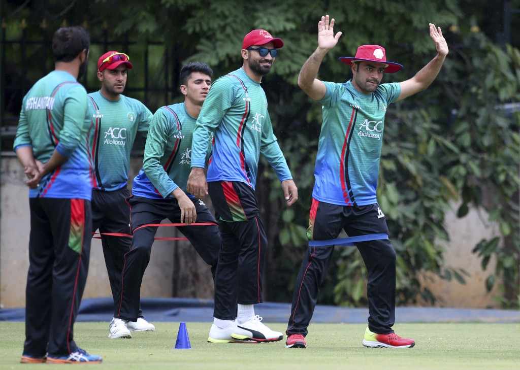 Afghanistan cricketer Rashid Khan, right, performs stretching exercises with teammates during a training session ahead of one-off test match against I