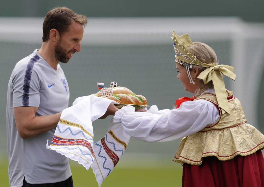England head coach Gareth Southgate, receives the traditional Russian greeting of bread from a woman in traditional costume before the start of the fi