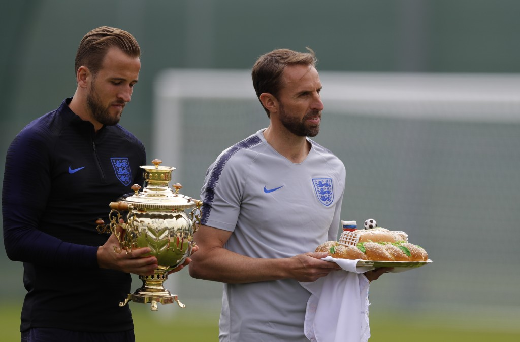 England head coach Gareth Southgate, holds a loaf of bread and England's Harry Kane holds a Russian tea urn they received during a traditional Russian