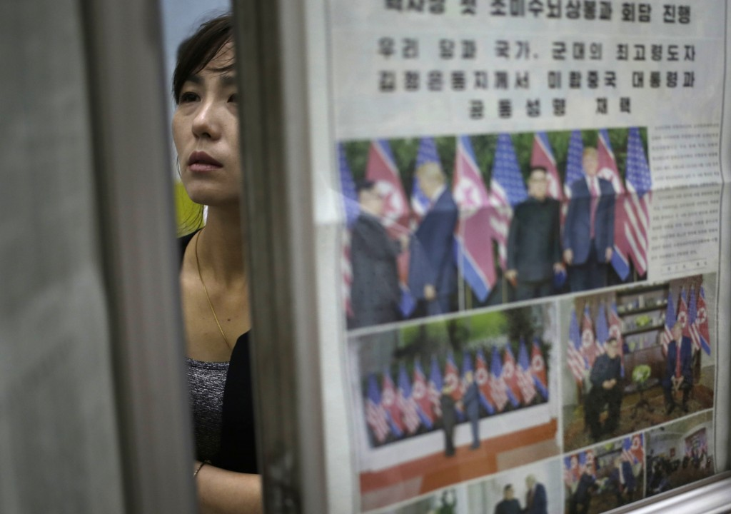 A woman reads newspapers fronting the news on US President Donald Trump's summit with North Korean leader Kim Jong Un at Puhung subway station in Pyon