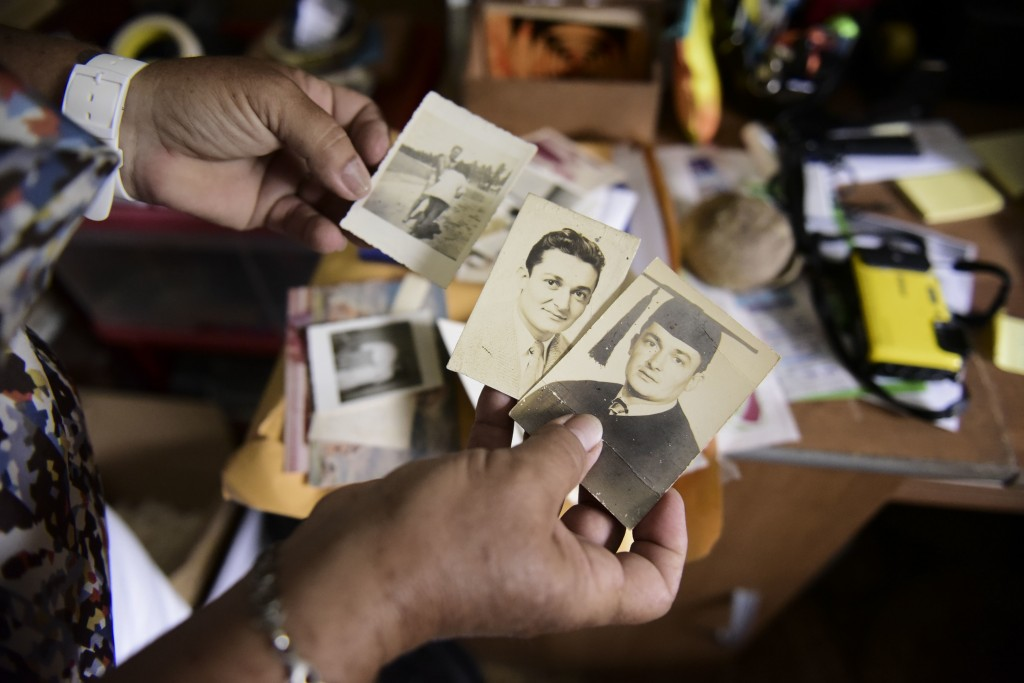 Nerybelle Perez holds several pictures of her father, World War II veteran Efrain Perez, who died inside an ambulance after being turned away from the...