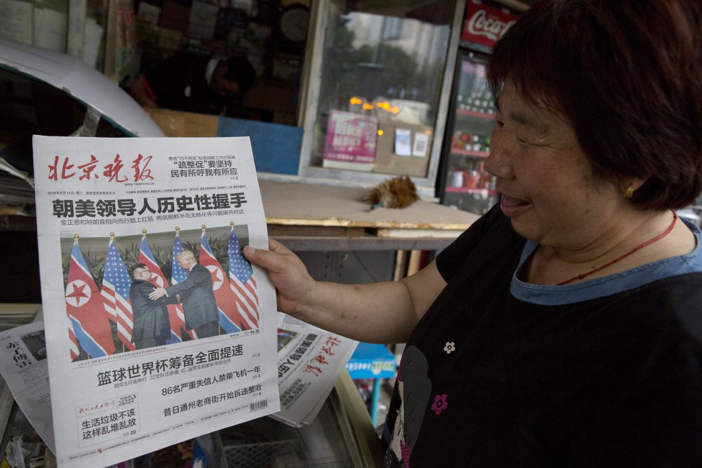 FILE - In this June 12, 2018, file photo, a newspaper vendor holds up a front page photo of the meeting in Singapore between U.S. President Donald Tru...