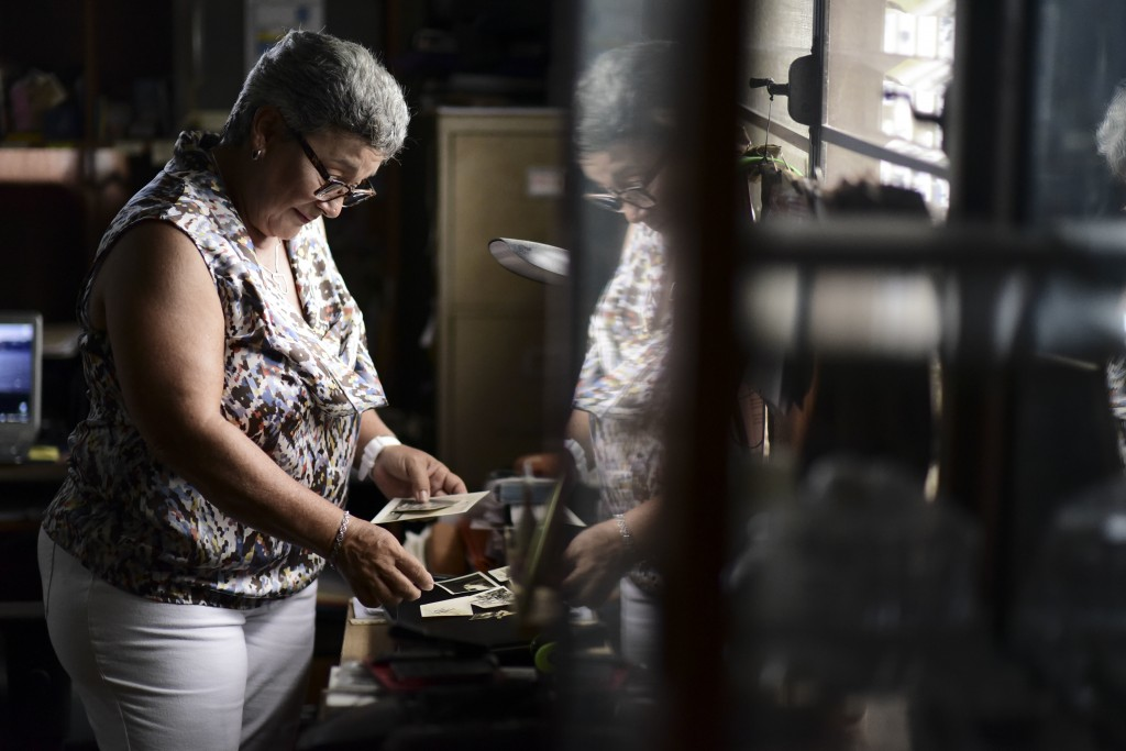 Nerybelle Perez goes through photographs of her father, World War II veteran Efrain Perez, who died inside an ambulance after being turned away from t...