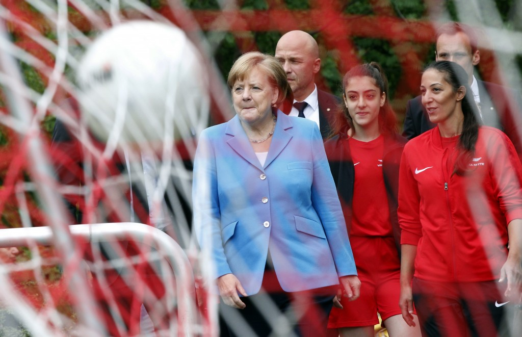 A ball flounces in the goal's net as German Chancellor Angela Merkel, center avrrives for a girls soccer training session at a soccer club in Berlin,