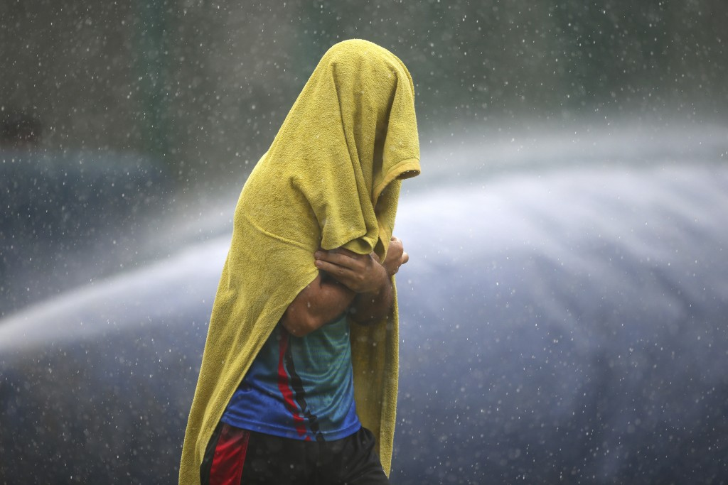 An unidentified player of Afghanistan cricket team covers himself with a towel as he runs for shelter during sudden rains at a training session ahead