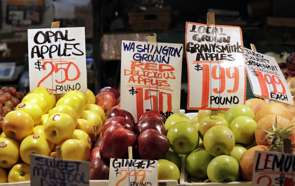 FILE- In this April 4, 2018, file photo apples grown in Washington state are displayed for sale at the Pike Place Market in Seattle. U.S. wholesale pr