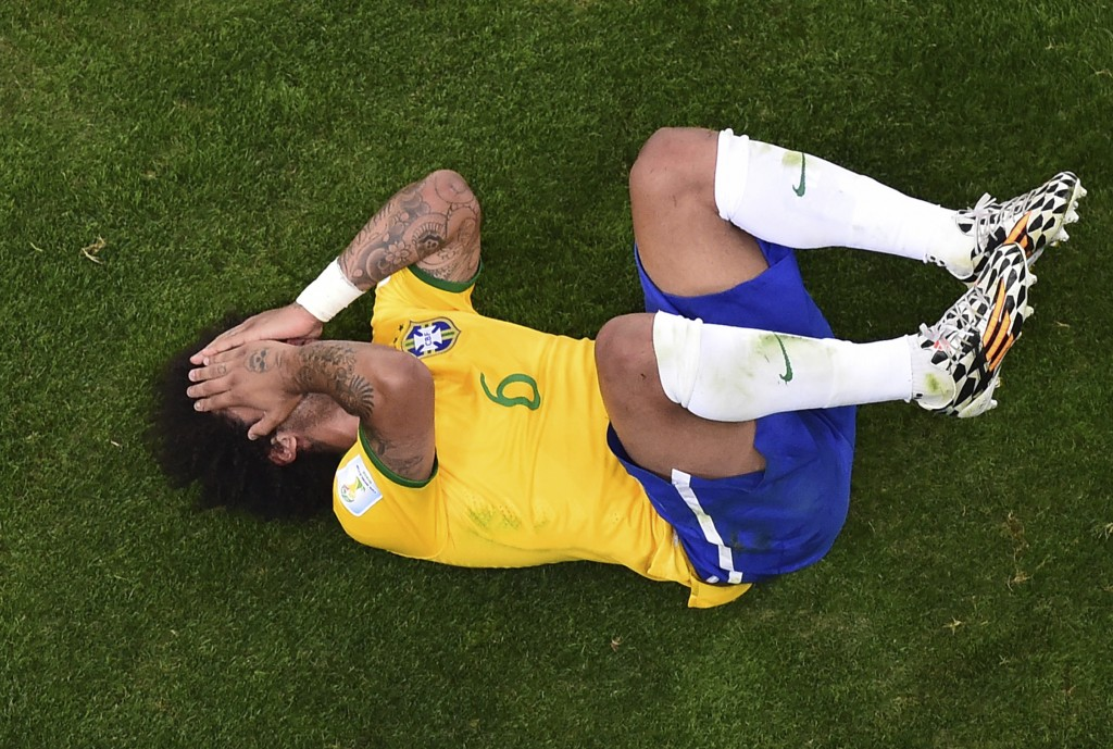 FILE - In this Tuesday, July 8, 2014 file photo, Brazil's Marcelo lies on the pitch during his team's 7-1 defeat in the World Cup semifinal soccer mat