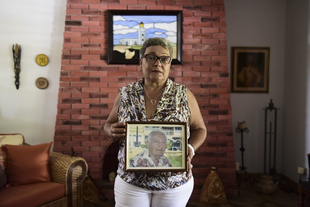 Nerybelle Perez poses with a portrait of her father, World War II veteran Efrain Perez, who died inside an ambulance after being turned away from the ...