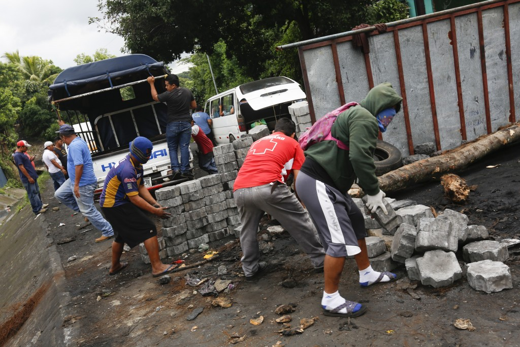 Anti-government protesters remove a roadblock they created so commercial vehicles can pass in Jinotepe, Nicaragua, Tuesday, June 12, 2018. Protests be