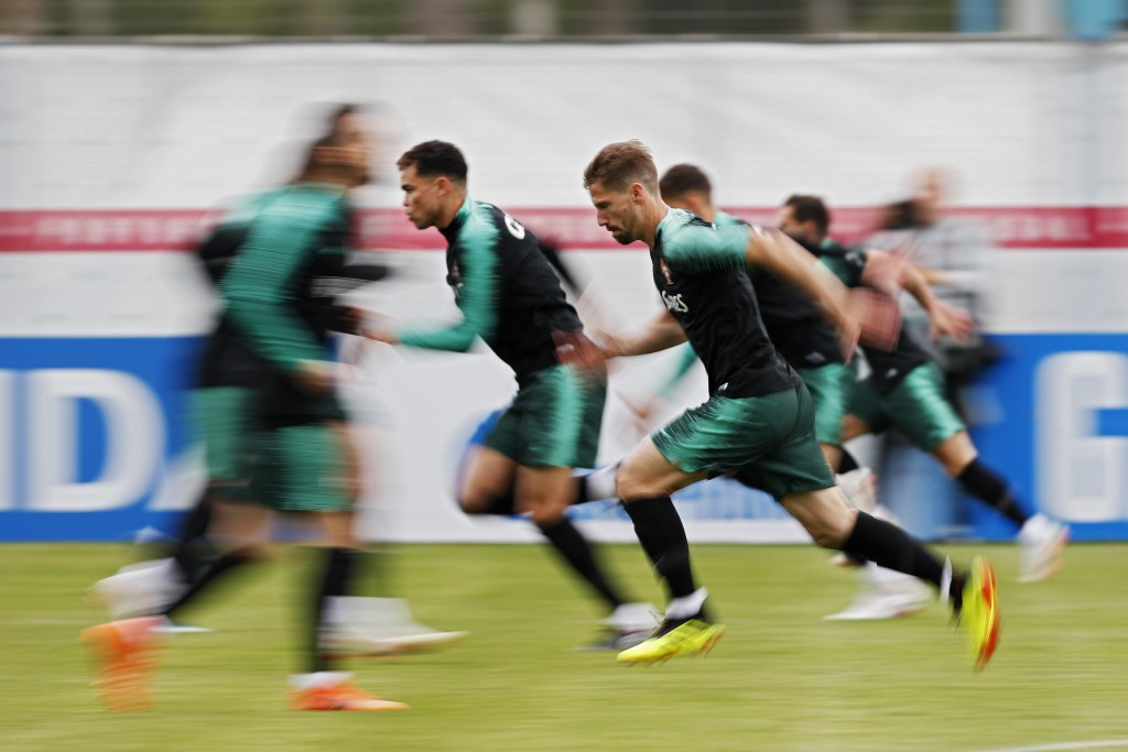 In this slow speed shutter photo, players run during the training session of Portugal at the 2018 soccer World Cup in Kratovo, outskirts Moscow, Russi