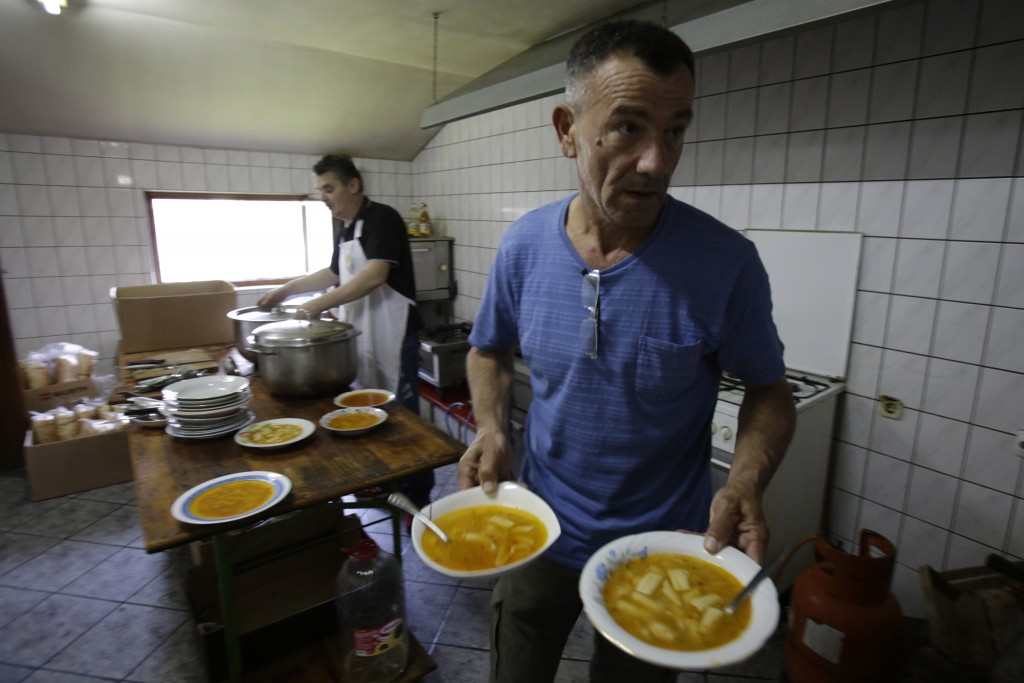 In this photo taken on Sunday, June 10, 2018, Bosnian people prepare lunch for migrants in Velika Kladusa, 400 kms north west of Bosnian capital of Sa