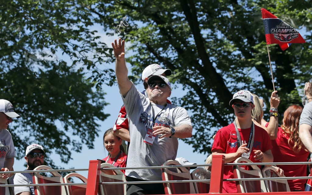 Washington Capitals coach Barry Trotz tosses a strand of beads during a victory parade for the NHL hockey Stanley Cup champions Tuesday, June 12, 2018...