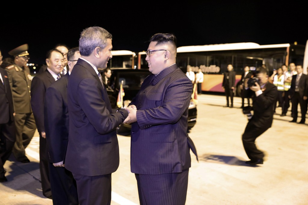 In this photo released by the Ministry of Communications and Information, Singapore, North Korean leader Kim Jong Un, center, is greeted before his de...