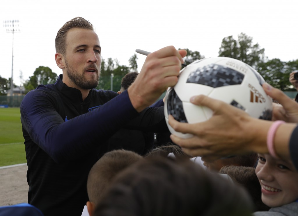 England's Harry Kane signs a ball for invited fans after a training session for the England team at the 2018 soccer World Cup in the Spartak Zelenogor