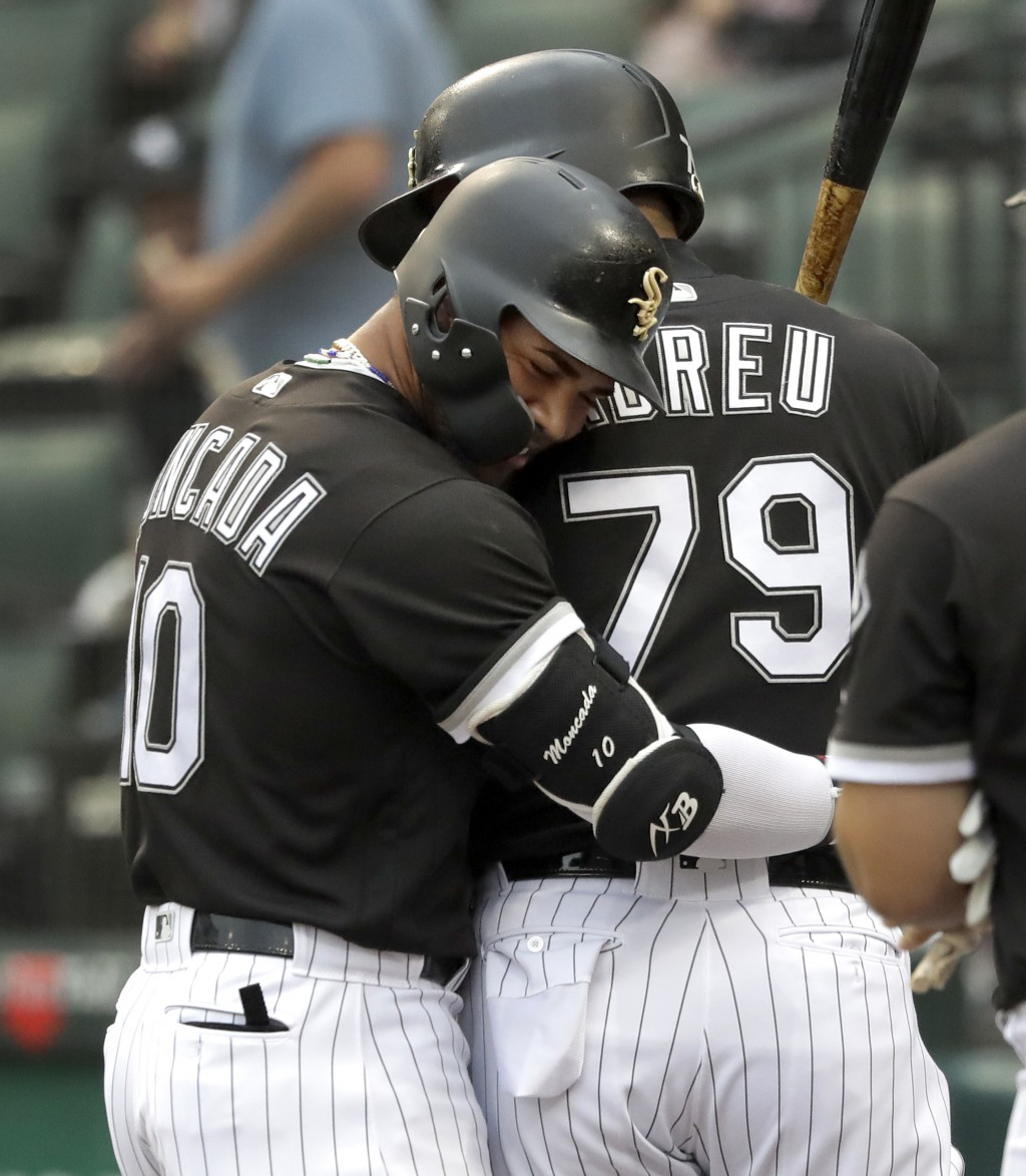 Chicago White Sox's Yoan Moncada, left, hugs Jose Abreu after Moncada's home run off Cleveland Indians starting pitcher Adam Plutko during the first i