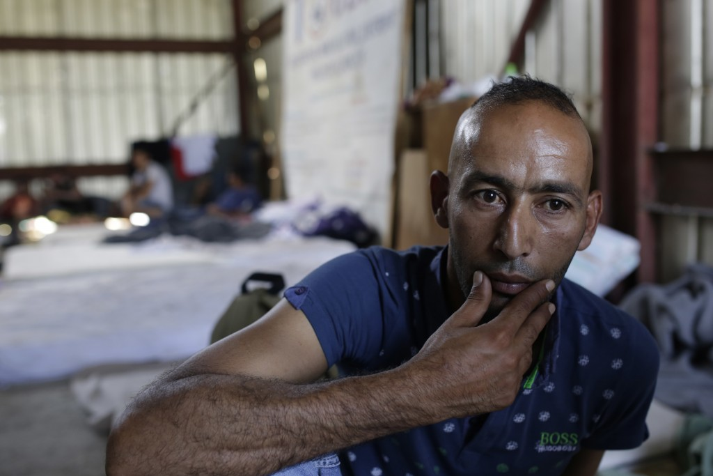 In this photo taken on Sunday, June 10, 2018, a migrant man from Libya waits in the shade of a warehouse for lunch, in Velika Kladusa, 400 kms north w