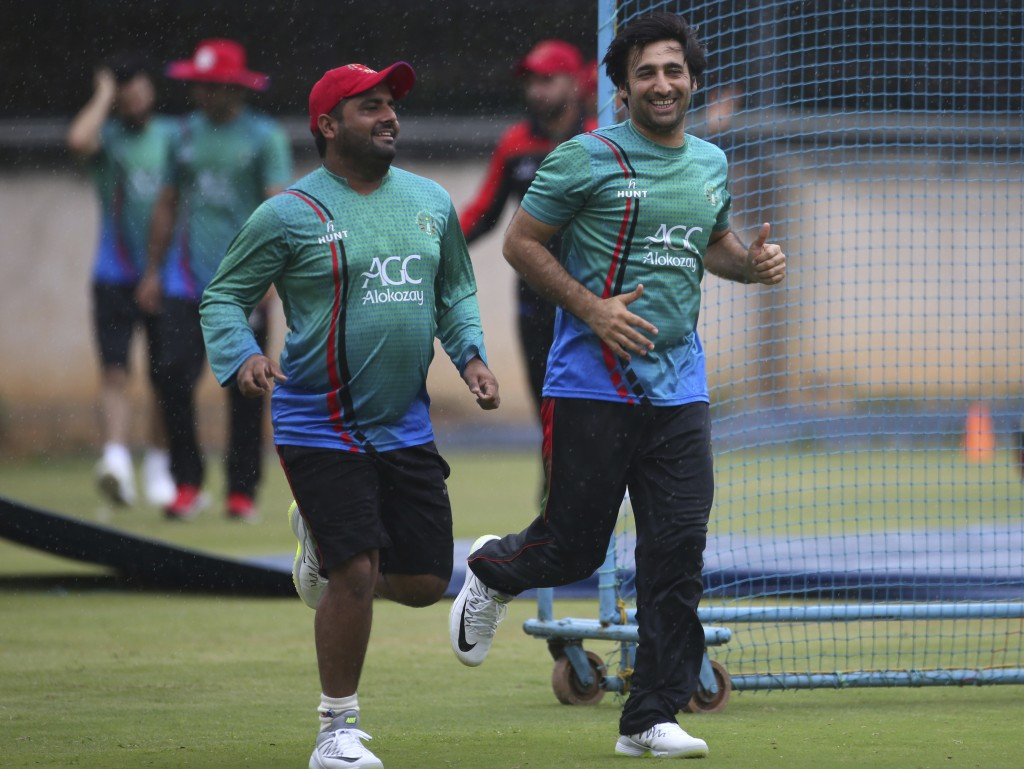 Afghanistan cricket team captain Asghar Stanikzai, right, and teammate Mohammad Shahzad run for shelter during sudden rains at a training session ahea