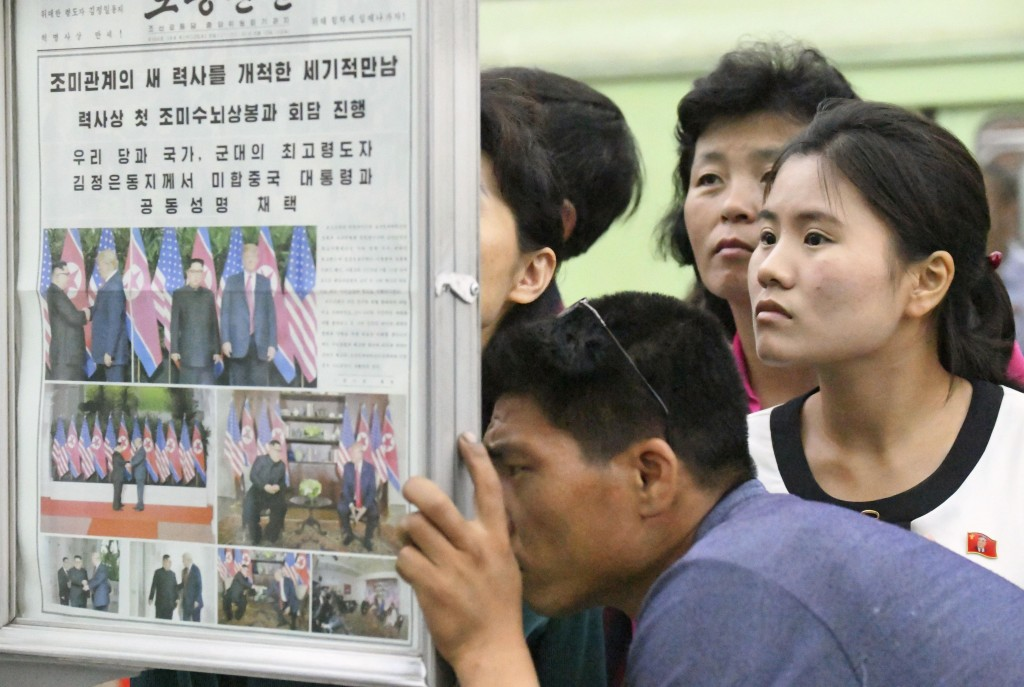 In this Tuesday, June 12, 2018, file photo, people look at a display of local newspaper reporting a meeting between North Korean leader Kim Jong Un an