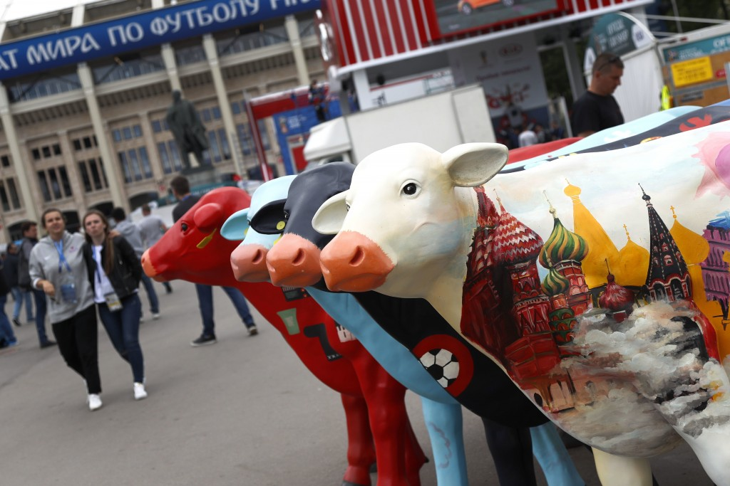 Colorfully painted advertising cows stand outside the stadium after the official training session of the Russian team one the eve of the group A match