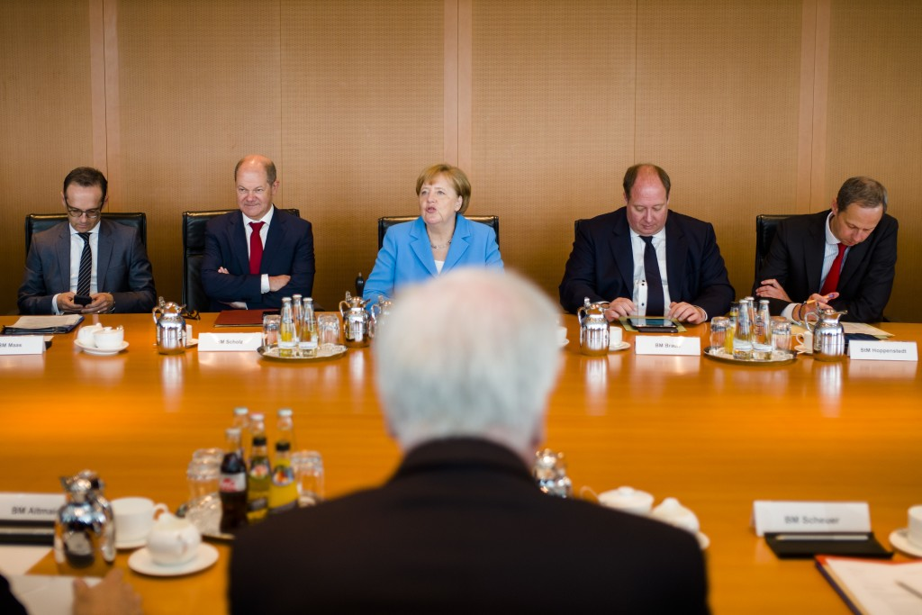 File - In this Wednesday, June 13, 2018 photo, German Interior Minister Horst Seehofer, front, sits on the opposite of German German Chancellor Angela