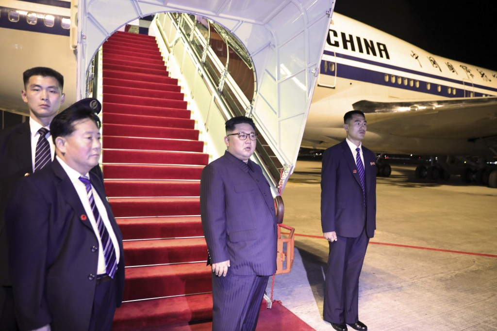 In this photo released by the Ministry of Communications and Information, Singapore, North Korean leader Kim Jong Un, center, stands before boarding t
