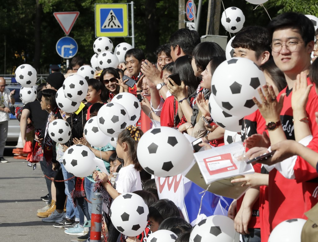 South Korean soccer fans hold soccer ball-shaped balloons upon South Korea's national soccer team's arrival at the team hotel for the 2018 soccer Worl
