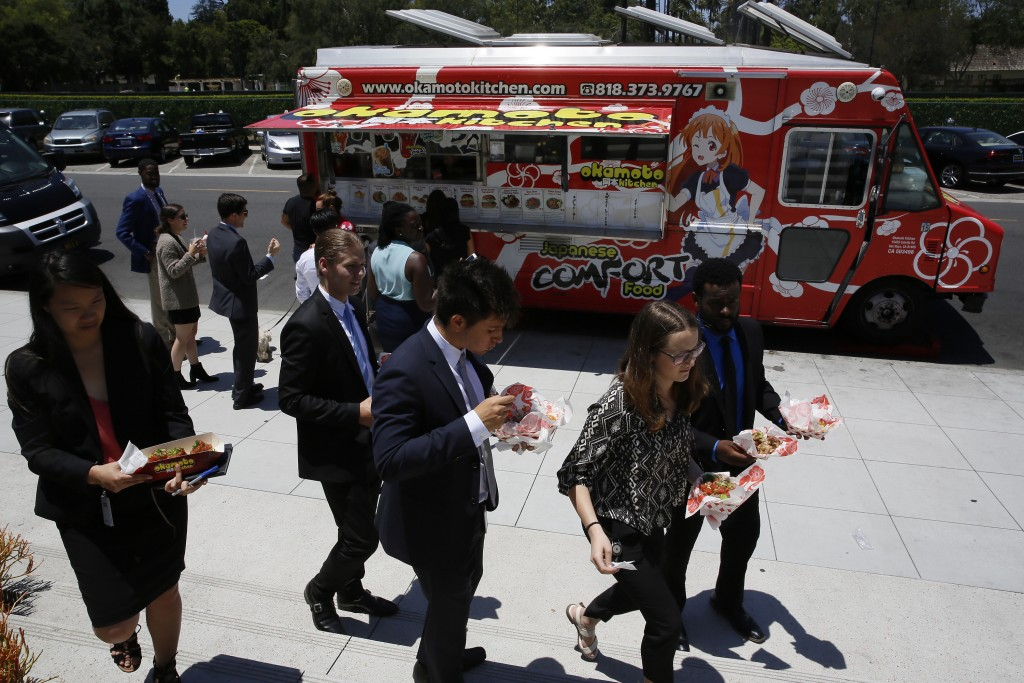 In this Friday, June 8, 2018, photo customers get their lunch at the Japanese food truck Okamoto Kitchen in Beverly Hills, Calif. Rather than sushi an