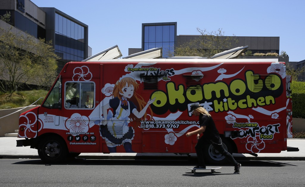 In this Friday, June 8, 2018, photo a skateboarder rides past the Japanese food truck Okamoto Kitchen in Beverly Hills, Calif. But Okamoto Kitchen has