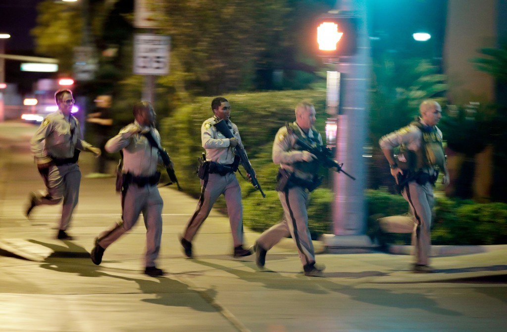 FILE - In this Oct. 1, 2017, file photo, police run toward the scene of a shooting near the Mandalay Bay resort and casino on the Las Vegas Strip in L