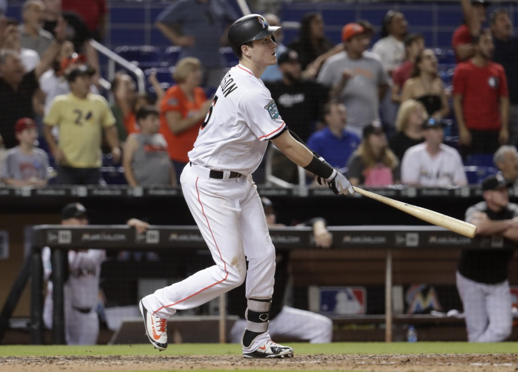 Miami Marlins' Brian Anderson watches his sacrifice fly that scored Miguel Rojas for the game-winning run during the ninth inning of a baseball game a