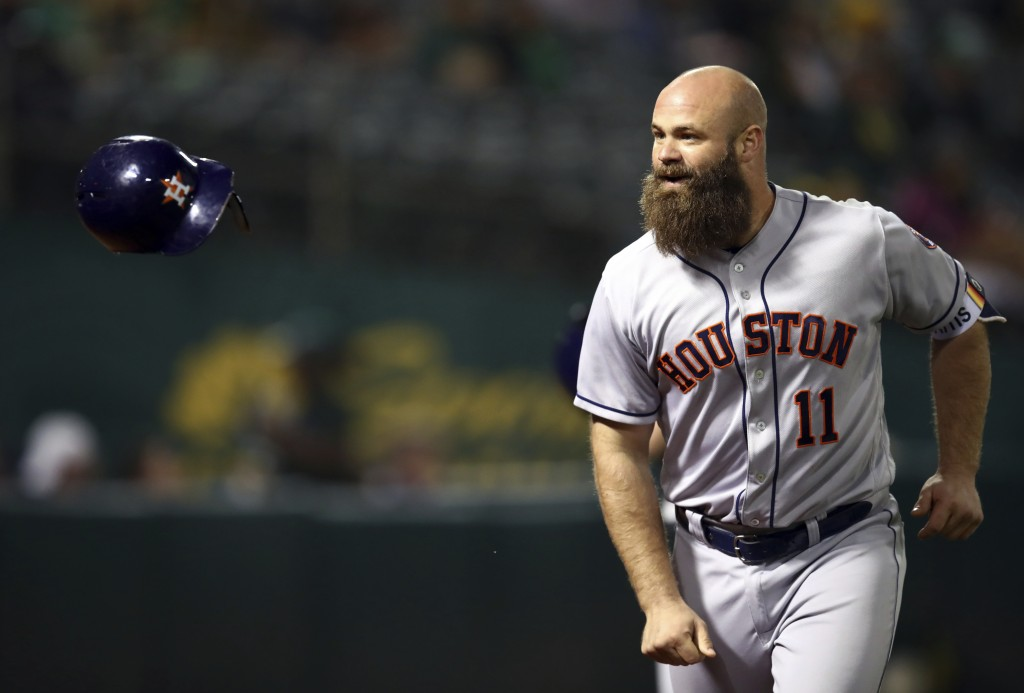 Houston Astros' Evan Gattis flips his helmet after hitting a home run off Oakland Athletics' Danny Coulombe during the seventh inning of a baseball ga