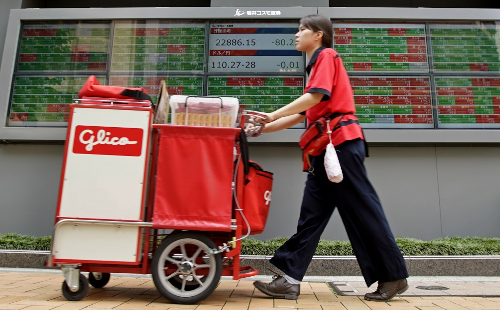 A drink vendor moves past an electronic stock board of a securities firm in Tokyo, Thursday, June 14, 2018. Asian stock markets slumped on Thursday wi