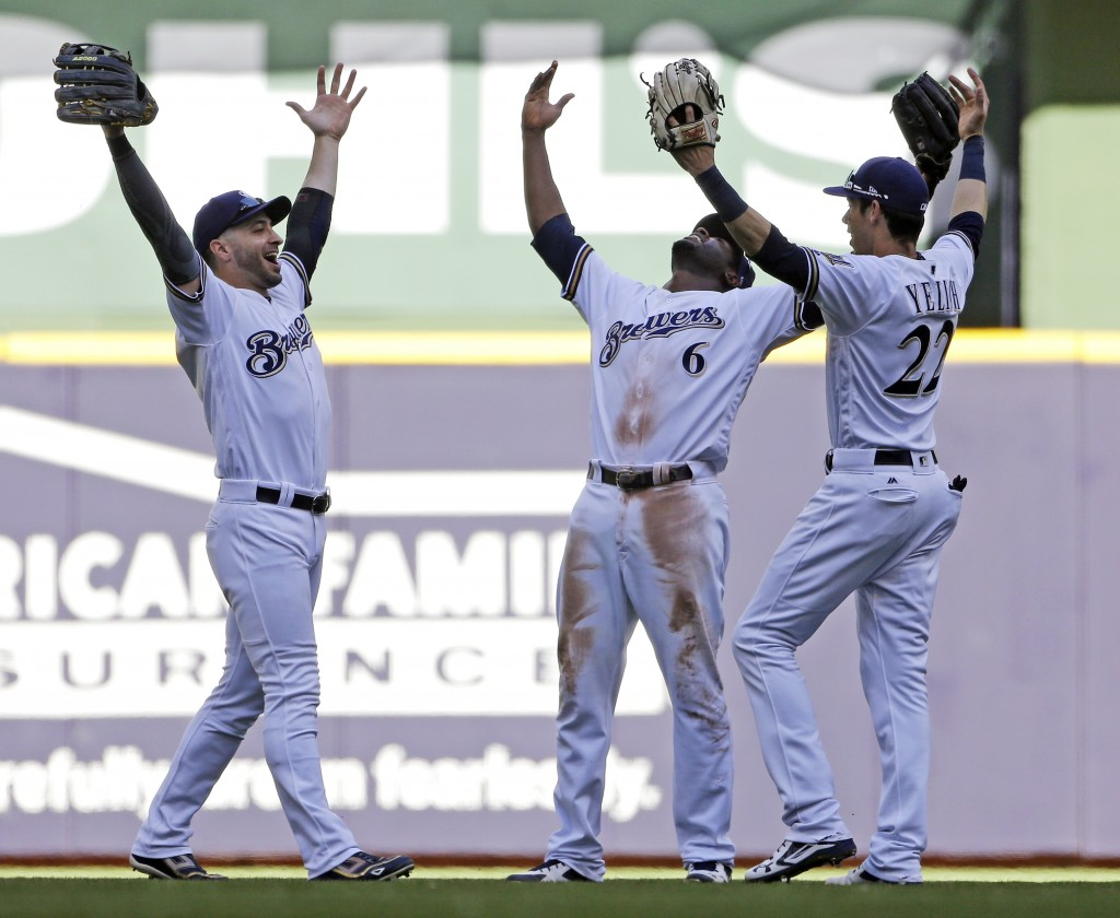 Milwaukee Brewers, from left, Ryan Braun, Lorenzo Cain and Christian Yelich celebrate after a baseball game against the Chicago Cubs, Wednesday, June