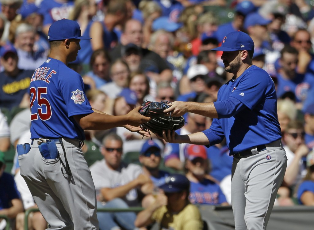 Chicago Cubs' Brian Duensing, right, exchanges gloves with Will Venable after being called in from playing the left field position to pitch during the
