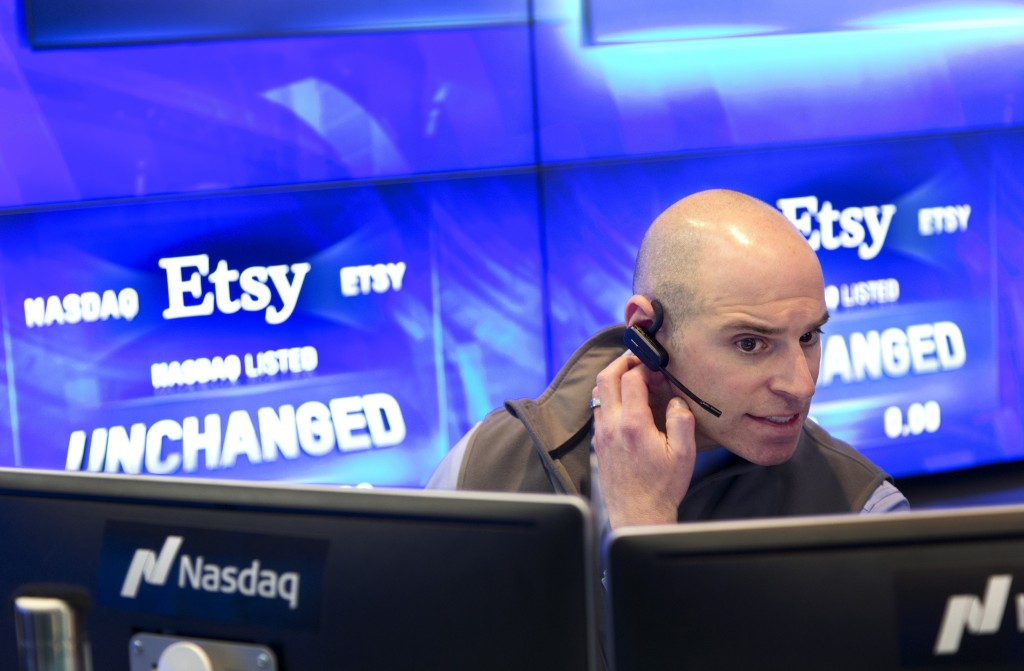 FILE- In this April 16, 2015, file photo, Jay Heller, the Nasdaq IPO Execution Officer, monitors Etsy's IPO at the Nasdaq MarketSite in New York. Etsy